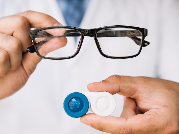 Male doctor showing pair of black glasses and contact lens Free Photo