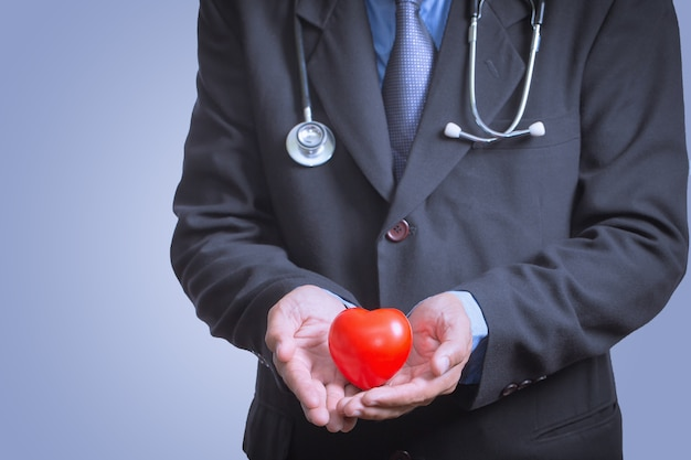 Male doctor showing stethoscope for checkup heart, heart care concept Premium Photo