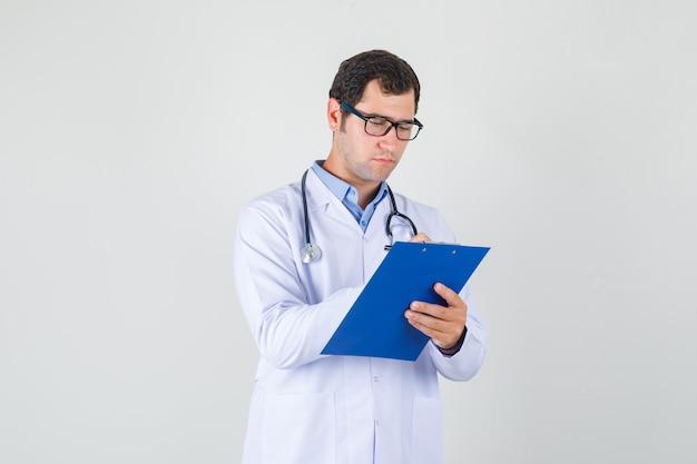 白衣、眼鏡、忙しそうに見えるクリップボードにメモを取る男性医師。正面図。 無料写真