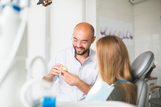 Male doctor talking to patient showing dental jaw Free Photo