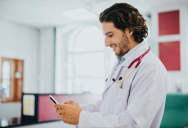 Male doctor using his smartphone Premium Photo