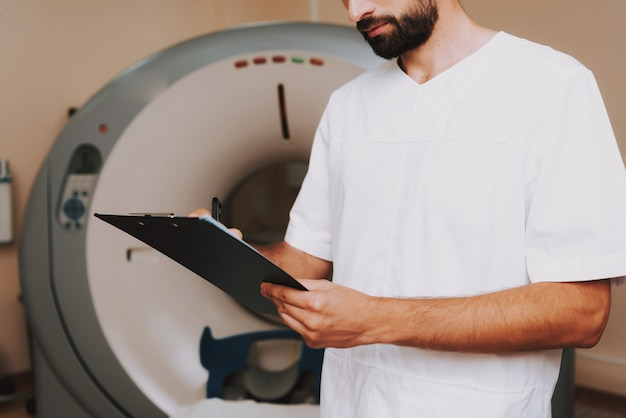 Male doctor with clipboard tomography machine Premium Photo