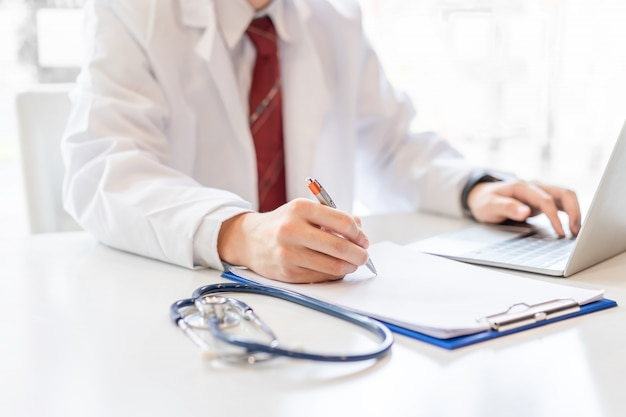 Male doctor working on desk with laptop. Premium Photo