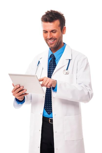 デジタルタブレットに取り組んでいる男性医師 無料写真