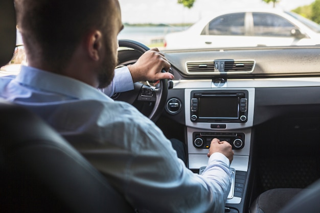 Male driver tuning radio in the car Free Photo