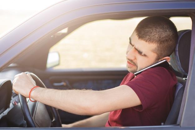 集中した表情の男性ドライバーが車を運転し、遠く離れた場所で重要な問題を解決して携帯電話で話します 無料写真