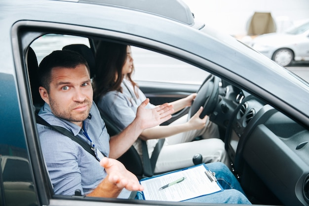 Male driving instructor shrugs up. man doesn't understand what his female student is doing. attractive blurred woman sits on driving seat, holds wheel and tries to concentrate Premium Photo