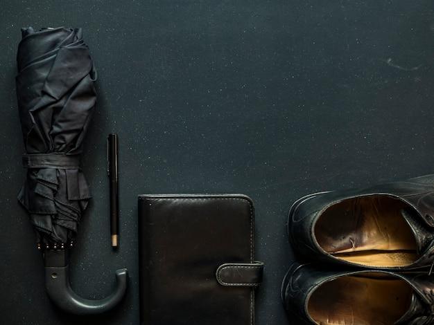 Male elegant trendy businessman supplies umbrella shoes notebook and pen copy space Premium Photo