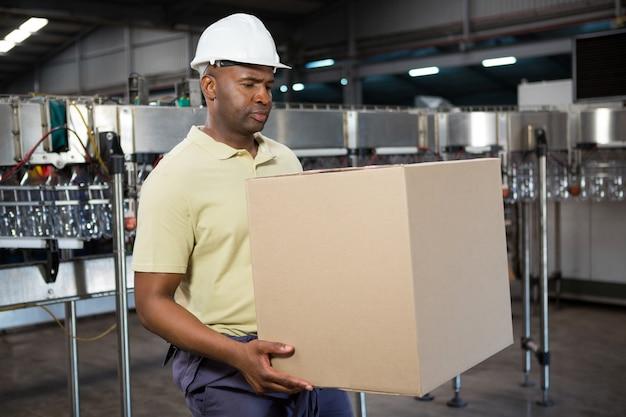ジュース工場で段ボール箱を運ぶ男性従業員 無料写真