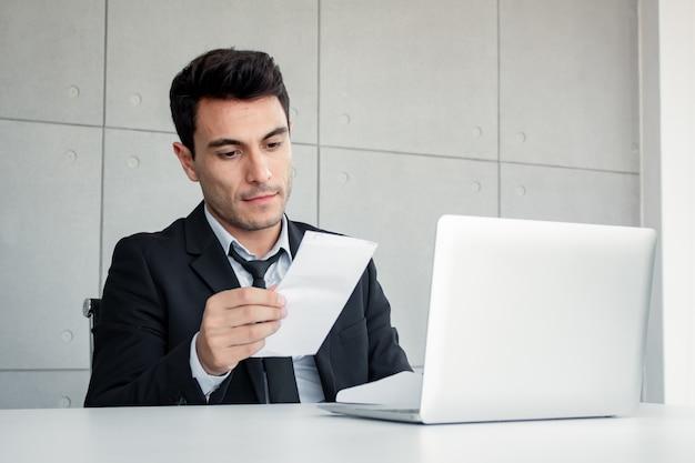 男性社員は懐疑的に文書を保持しています。 Premium写真