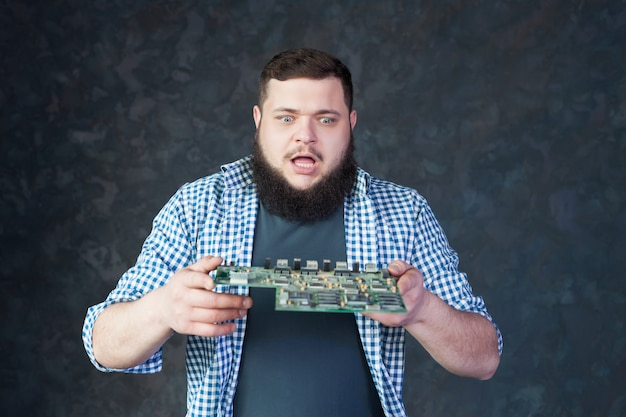Male engineer blows off the dust from motherboard Premium Photo