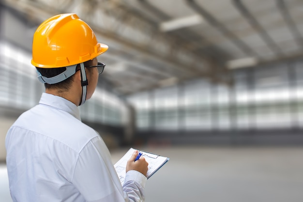 Male engineer checking in factory with note on notepad or industry Premium Photo
