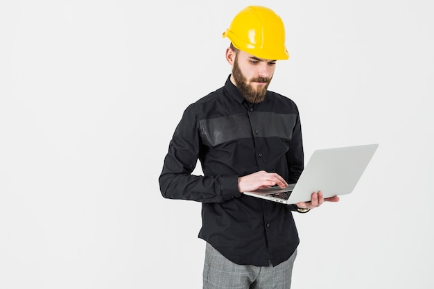 Male engineer wearing hardhat using laptop against white background Free Photo