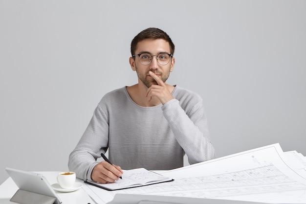 남성 엔지니어는 느슨한 캐주얼 스웨터와 둥근 안경을 착용하고 직장에 앉아 있습니다. 무료 사진