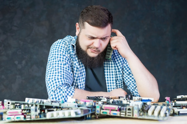 Male engineer work with broken computer motherboard. electronic devices repairing technology Premium Photo