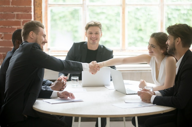 Male executive shaking hands with female coworker, teamwork introduction. Free Photo