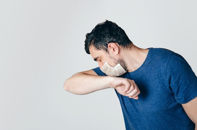 Male in the face mask sneezing Premium Photo