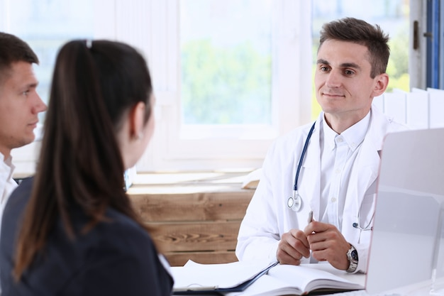 Male family doctor listen carefully young couple in office Premium Photo