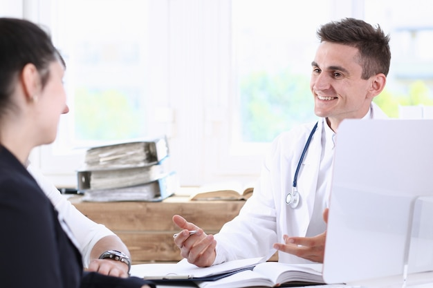 Male family doctor listening carefully young couple in office portrait. Premium Photo