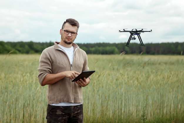 A male farmer manages a drone over agricultural land. Premium Photo