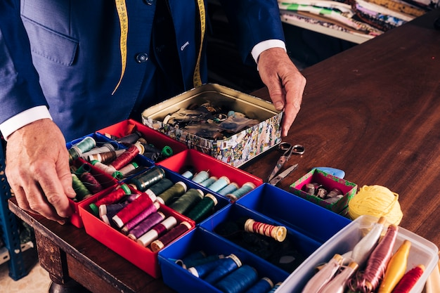 Male fashion designer's hands on container containing different type of thread spools on wooden table Free Photo
