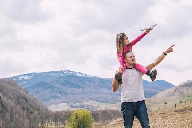 男性の父と手に白いおもちゃの飛行機を持つ小さな女の赤ちゃん Premium写真