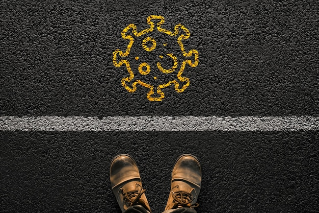 Male feet with shoes stands on the asphalt with a line and a virus from yellow paint. travel and covid concept. infection and pandemic Premium Photo