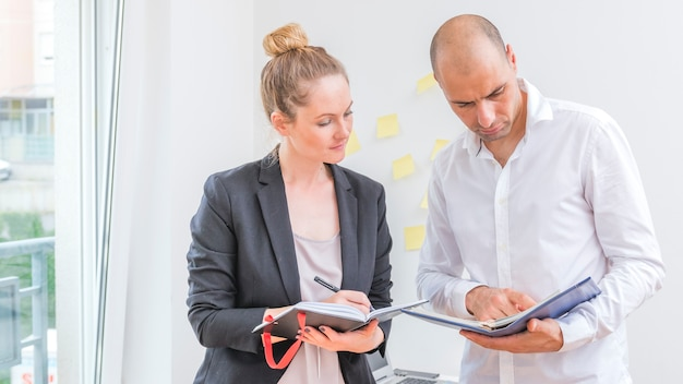 Male and female businesspeople looking at schedule in diary Free Photo