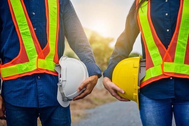 Male and female engineer holding hardhat safety Premium Photo