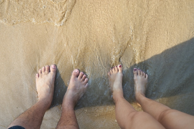 Male and female feet standing on the beach | Premium Photo