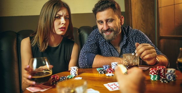 Male and female friends sitting at wooden table. men and women playing card game. hands with alcohol close-up. poker, evening entertainment and excitement concept Free Photo