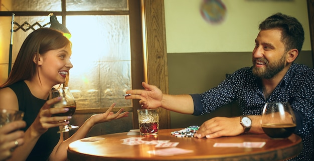 Male and female friends sitting at wooden table. men and women playing card game. hands with alcohol close-up. Free Photo