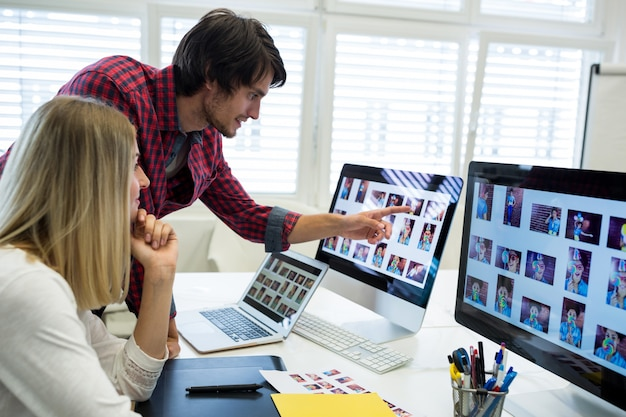 Male and female graphic designers interacting over computer Free Photo