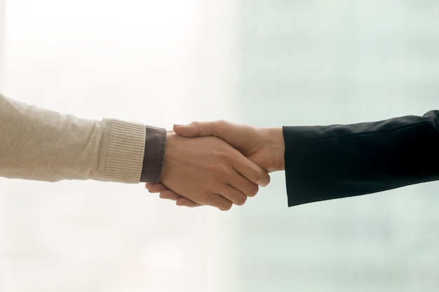 Male and female hands shaking, business handshake with copy space Free Photo