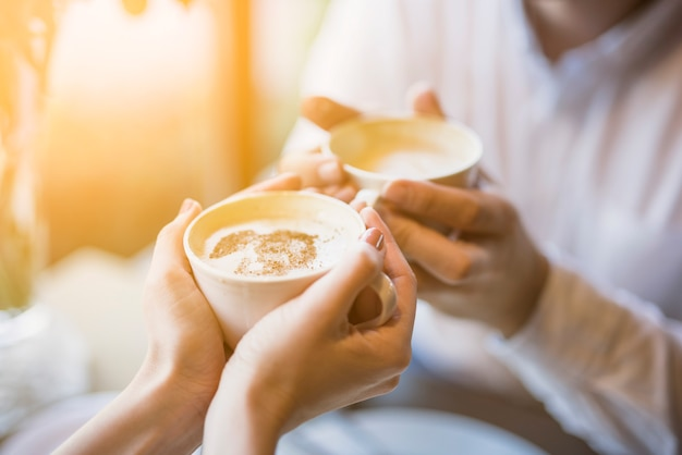 Male and female holding cups of hot drink Free Photo