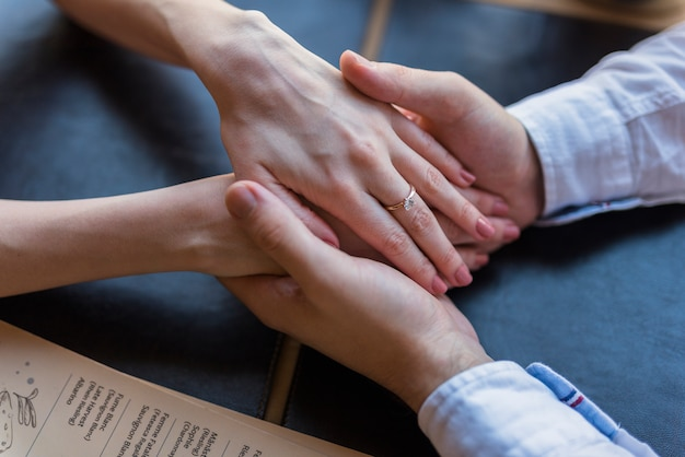 Male and female holding hand at table Free Photo