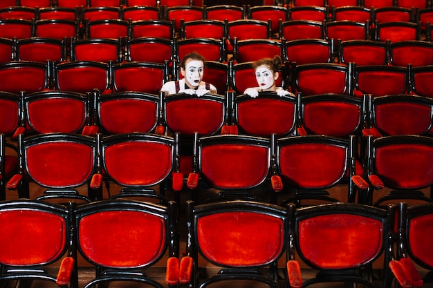 Male and female mime artist hiding behind the row of arm chairs Free Photo