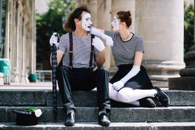 Male and female mime artist sitting on staircase Free Photo