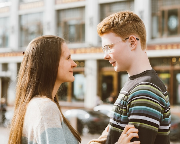 Male and female person looking at each other, young couple full of love. the redhead boy Premium Photo