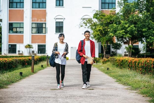 Le studentesse e gli uomini indossano il viso chill e sono in piedi di fronte all'università. Foto Gratuite