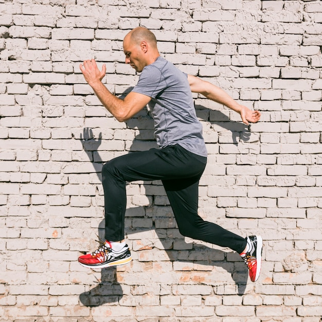Male fitness athlete young man jumping in air against white painted wall Free Photo