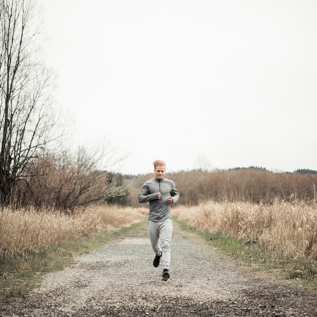 Male fitness young man running on dirt road over the field Free Photo