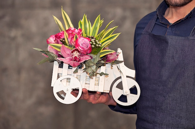Male florist promoting a car shaped mixed flower basket. Free Photo