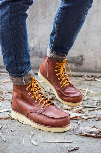 Male foot with brown leather shoes and jeans Free Photo