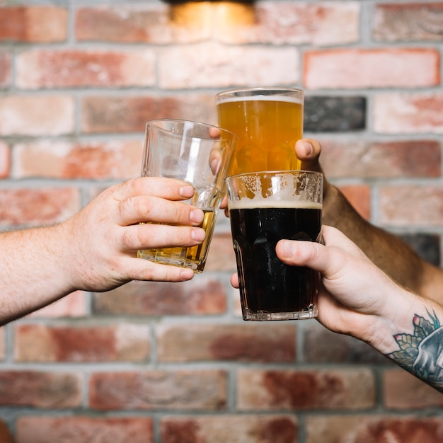 Male friend's hand toasting glasses of alcoholic drinks against brick wall Free Photo