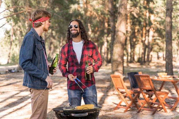 ビールとバーベキューで会話する男性の友人 無料写真