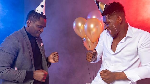 Друзья-мужчины танцуют на вечеринке Premium Фотографии