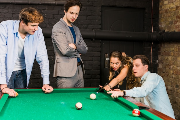 Male friends looking at woman playing snooker in club Free Photo