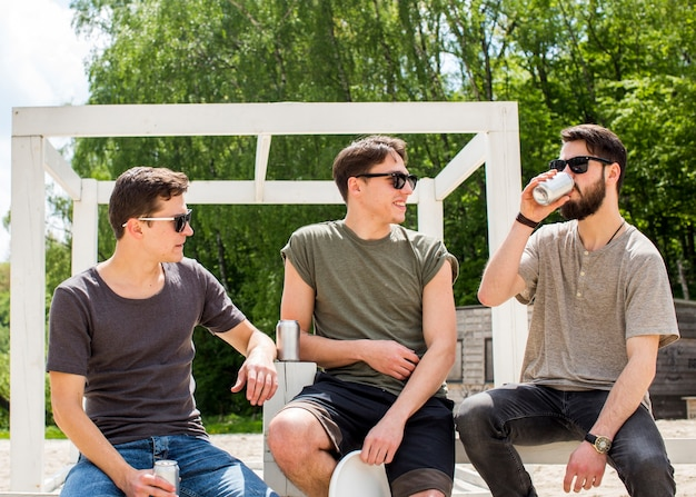 Male friends relaxing with refreshing drinks Free Photo