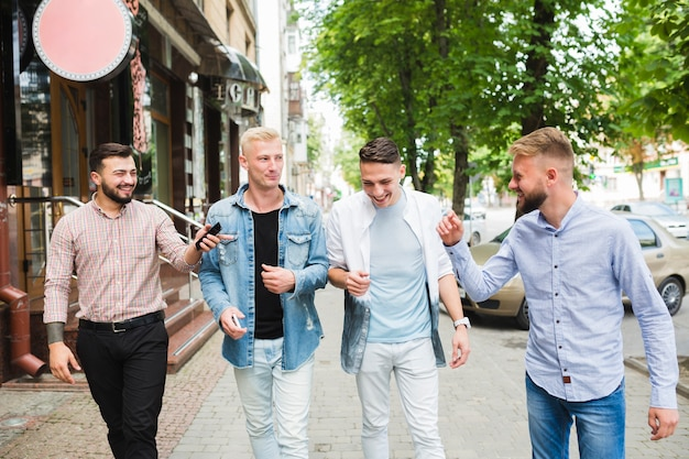 male friends walking together on city street enjoying photo free